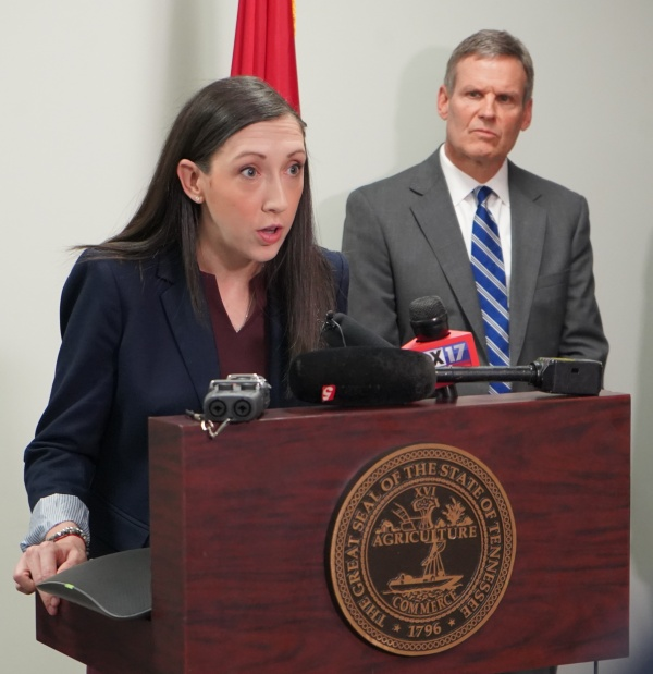 Mary-Margaret Fill, MD, speaks at a lectern before TV cameras as Gov. Bill Lee looks on.