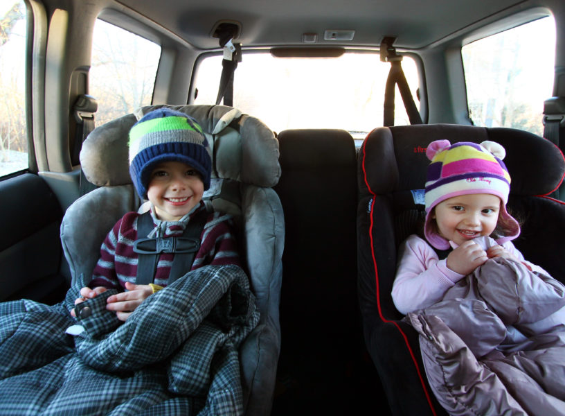 child in car seats with coats on their laps