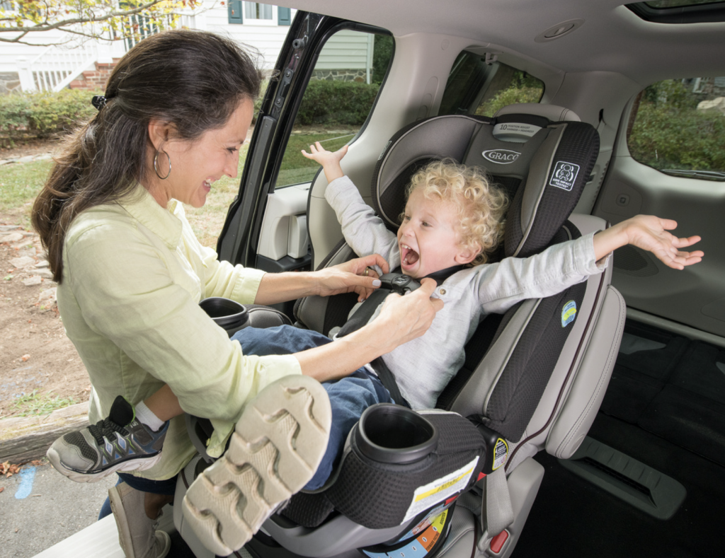 mom putting child in car seat and the child is excited