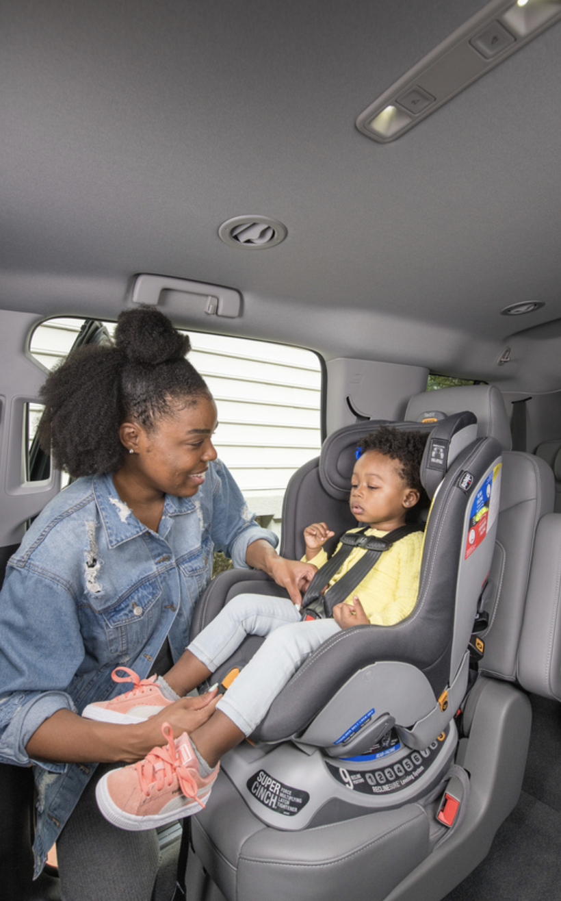 Mom placing child in car seat