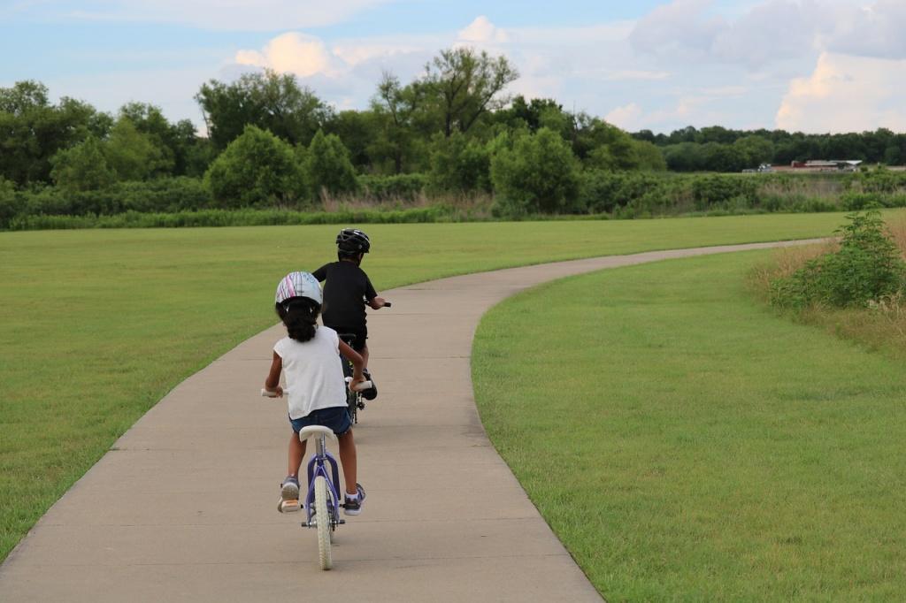 two kids biking with helmets