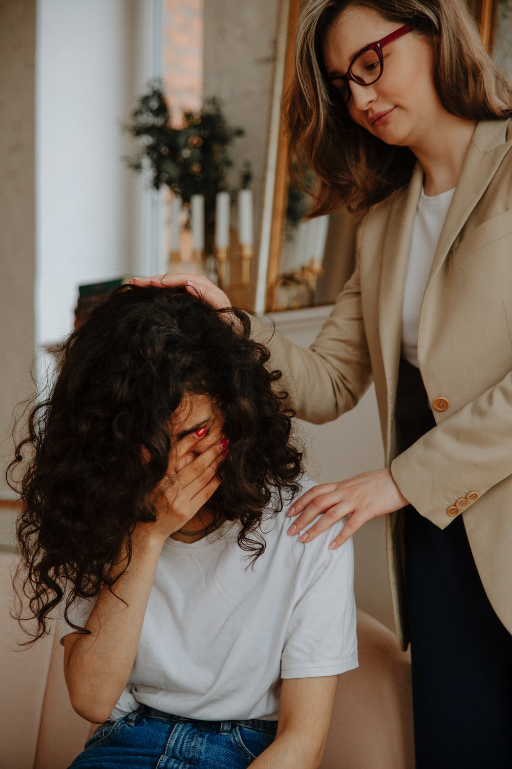 mother comforting teen daughter crying