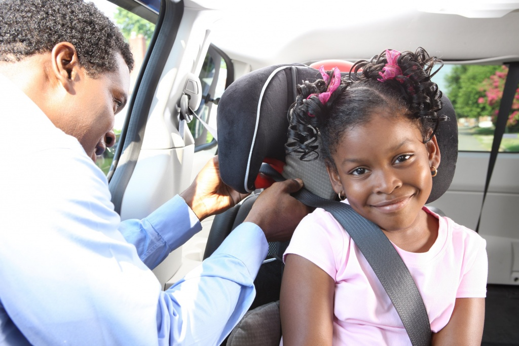 dad helping daughter with car seat