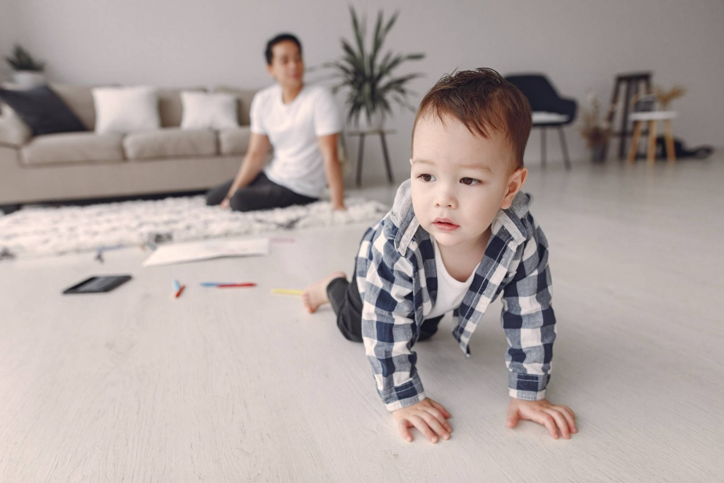 child crawling with adult in background