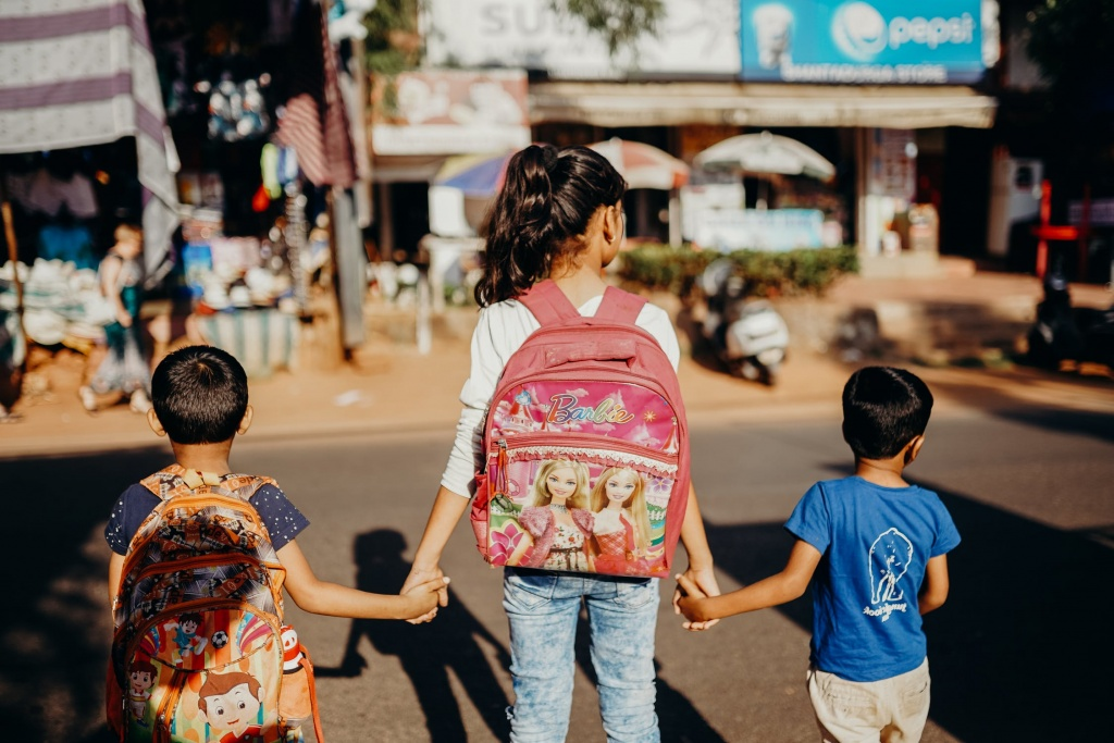 3 kids hold hands with backpacks